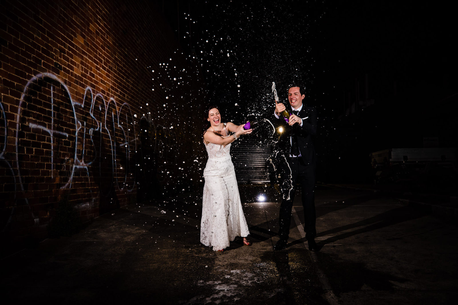 bride and groom spraying champagne