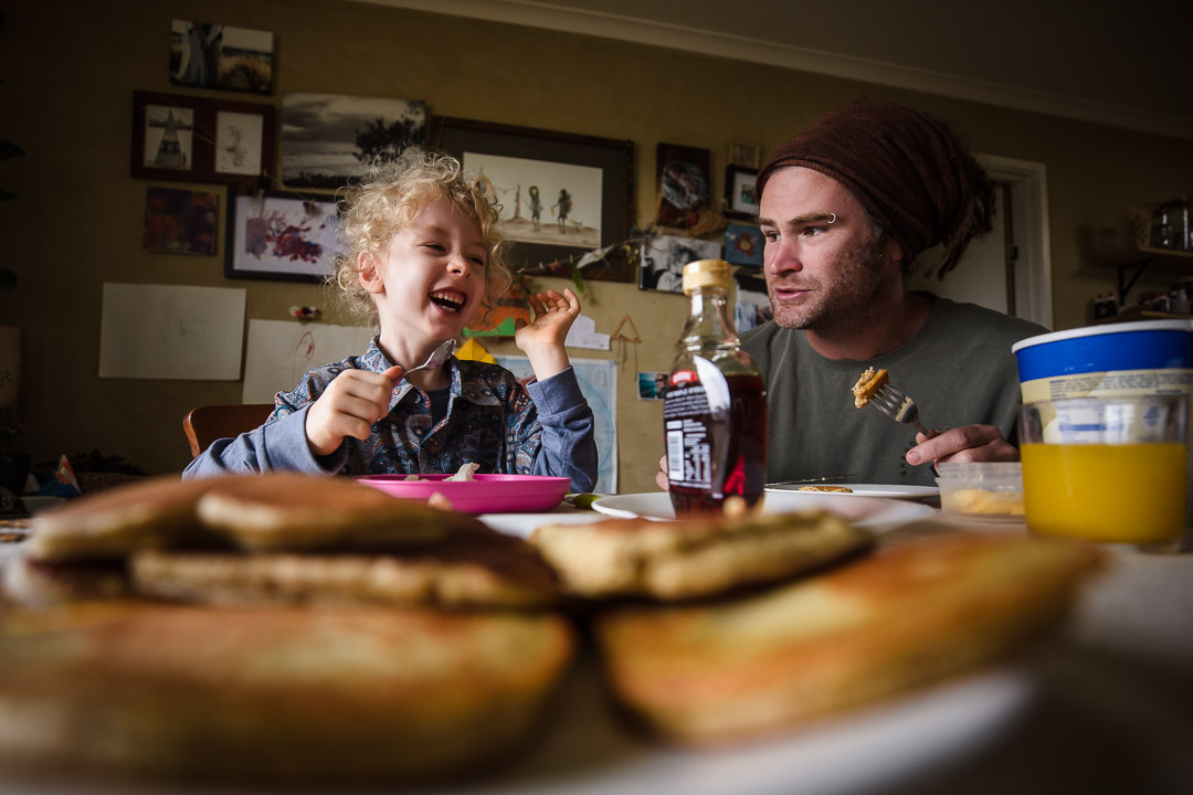 father and son eating pancakes together during family videography session at home